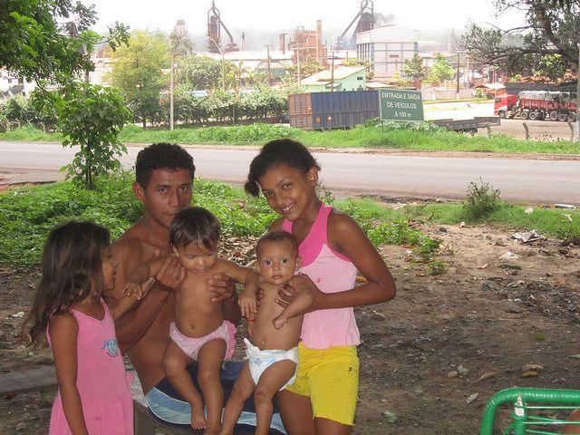 Una familia sonríe a la cámara mientras se protege del calor a la sombra de un árbol. La carretera la separa de la industria del arrabio, que hace imposible la vida en el barrio. Crédito: Mario Osava/IPS