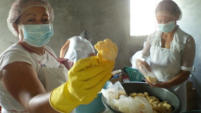 Patricia Pineda, en primer plano, y Roxana Ramírez, mientras preparan encurtidos de hortalizas en el municipio salvadoreño de San Isidro. Proyectos como este pretenden ser una alternativa económica a la minería en la zona. Crédito: Edgardo Ayala/IPS
