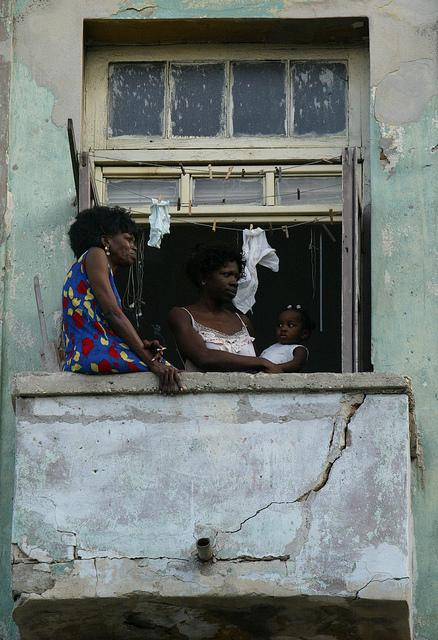 Tres afrocubanas, abuela, madre y nieta, en el balcón de su vivienda en La Habana, en Cuba. Las mujeres negras sufren doble discriminación en el país. Crédito: Jorge Luis Baños /IPS
