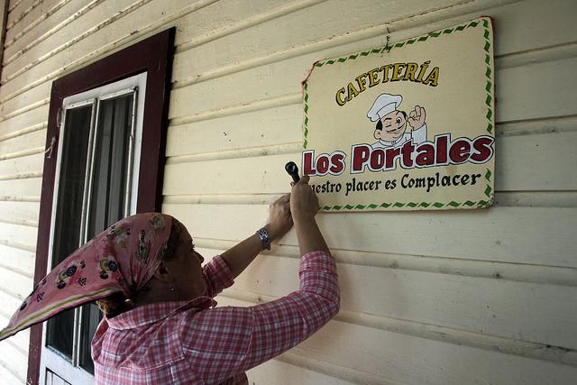 La propietaria de la cafetería Los Portales coloca un cartel para identificar su establecimiento en Jesús Menéndez, un municipio del oriente cubano. La tributación de los negocios privados engrosará desde ahora las arcas municipales, para mejorar las condiciones de cada localidad. Crédito: Jorge Luis Baños/IPS