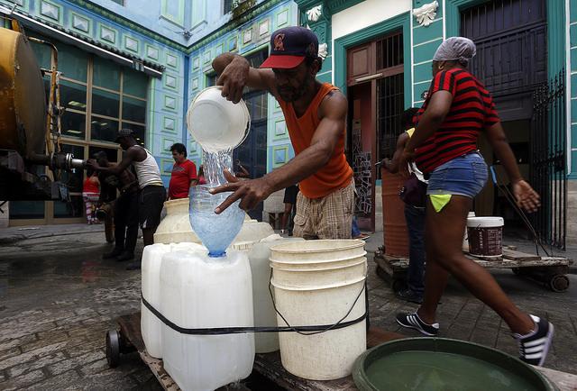 Un hombre  llena varios envases con agua potable procedente de un camión cisterna, en una calle de La Habana Vieja, en la capital de Cuba. Las dificultades del abastecimiento del recurso a los hogares, por problemas estructurales en la red de suministro y una aguda sequía,  trastoca la vida de los habitantes de La Habana, en especial de las mujeres. Crédito: Jorge Luis Baños/IPS