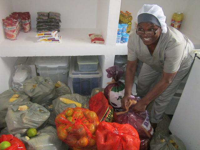La cocinera Penha Maria Flausina abre los sacos recién entregados por agricultores familiares, con frutas y hortalizas, en la Escuela Municipal João Baptista Cáffaro, con 500 alumnos de enseñanza primaria, en un barrio carenciado de la ciudad de Itaboraí, en el sureste de Brasil. Crédito: Mario Osava/IPS