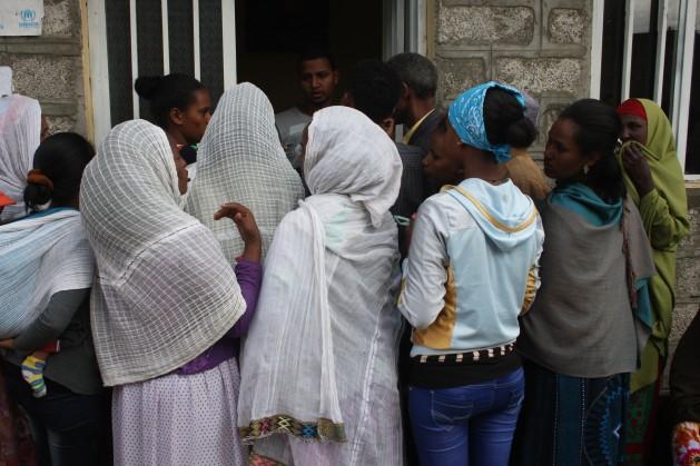 En el centro del Servicio Jesuita para los Refugiados de Etiopía, los refugiados, en su mayoría mujeres, retiran mantas, arroz y aceite comestible. Crédito: James Jeffrey/IPS.