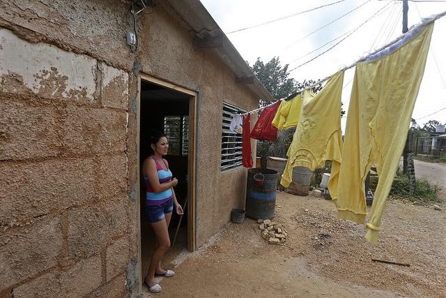 Yelenis Irán, de 32 años, quien trabaja en un hotel del balneario de Varadero,  posa a la entrada de su vivienda, construida en el asentamiento informal de La Cartonera, en el extrarradio de la  ciudad de Cárdenas, en Cuba, a donde migró con su familia desde el oriente del país. Crédito: Jorge Luis Baños/IPS