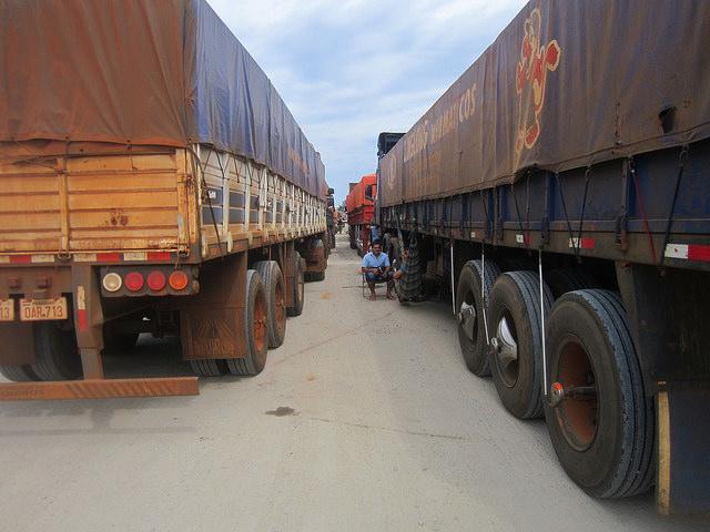 Dos choferes descansan mientras esperan a descargar sus camiones  en el Complejo Agroindustrial Angostura (Caiasa), procesador de soja en Paraguay. Unos 2.000 camiones transportan la leguminosa hasta la planta, que en la época de zafra recibe en promedio 500  vehículos de gran tonelaje, cuya descarga no demora más de un día en las fechas más intensas. Crédito: Mario Osava/IPS