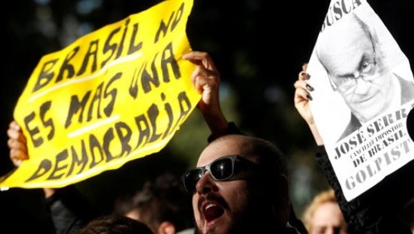 """""""Brasil no es más una democracia"""", rezaba un cartel de uno de los manifestantes que protestaron el 23 de mayo en Buenos por la visita del canciller de ese país, José Serra, a quien en otro cartel con su fotografía calificaban de golpista. Crédito: TelesurTV"""