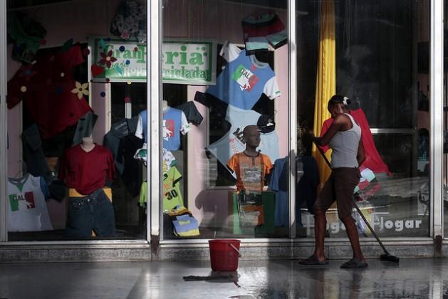 Una mujer afrodescendiente realiza labores de limpieza en el exterior de una tienda en el centro de La Habana. Los activistas antirracistas indican que las personas afrocubanas enfrentan formas de discriminación laboral. Crédito: Jorge Luis Baños/IPS