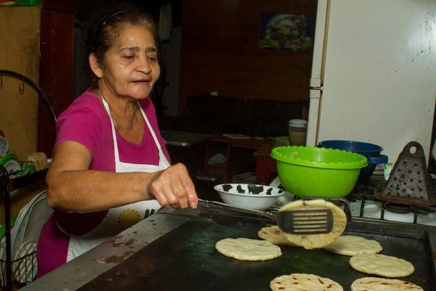 Juana Morales prepara popusas en su cocina. Una especie de tortillas, que los salvadoreños comen rellenas con variados productos, no son hechas con harina de maíz, sino con ojushte, una semilla muy nutritiva, cuyo consumo se promueve en el pueblo de San Isidro, en el occidente de El Salvador. Crédito: Edgardo Ayala/IPS