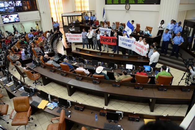"""Con pancartas como """"Farsa no"""", diputados opositores protestan en la Asamblea Nacional de Nicaragua, el 15 de junio, contra medidas como la exclusión de observadores y de la coalición opositora en las elecciones de noviembre. Días después los 28 diputados opositores fueron expulsados del parlamento. Crédito: Manuel Esquivel /IPS"""