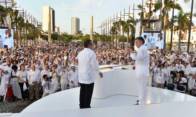 """El presidente Juan Manuel Santos (derecha) le muestra al jefe de las FARC, Rodrigo Londoño, el simbólico """"baligrafo"""" con el que ambos firmaron el Acuerdo Final de Paz de Colombia. Crédito: Presidencia de Colombia"""
