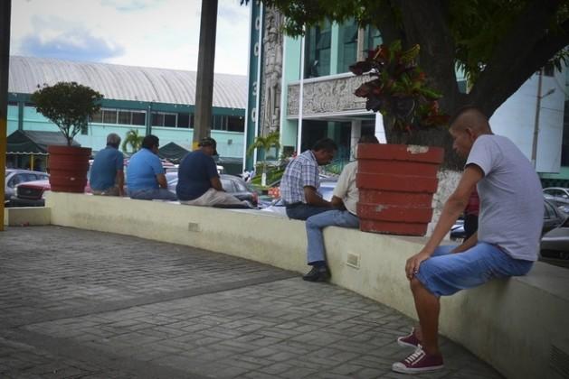 Algunos hombres pasan el tiempo sentados en un muro, frente a la Sección 30 del sindicato petrolero, en la oriental ciudad de Poza Rica, en México. Crédito: Edgar Escamilla/Pie de Página