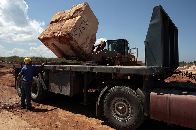 Trabajadores colocan en un camión, con ayuda de una pala mecánica, un bloque de mármol, extraído en la Cantera de Piedra Jaimanitas, en Salado, en la occidental provincia de Artemisa, en Cuba. Crédito: Jorge Luis Baños/IPS