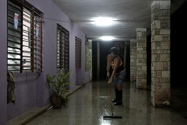 Una trabajadora limpia el suelo del corredor de una vivienda en Wajay, en el oeste de La Habana, en Cuba. El empleo en el servicio doméstico crece en el país, realizado casi siempre por mujeres, solo durante el día y muchas veces de manera informal. Crédito: Jorge Luis Baños/IPS