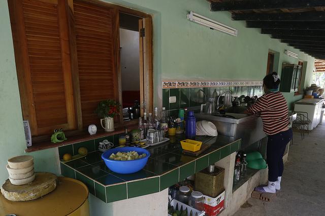 Una empleada doméstica lava algunos utensilios en la  Finca Marta, en el municipio de Caimito, en la occidental provincia de Artemisa, en Cuba. El trabajo en el servicio doméstico, por mucho tiempo casi desaparecido en el país, se ha extendido también a las zonas rurales. Crédito: Jorge Luis Baños/IPS