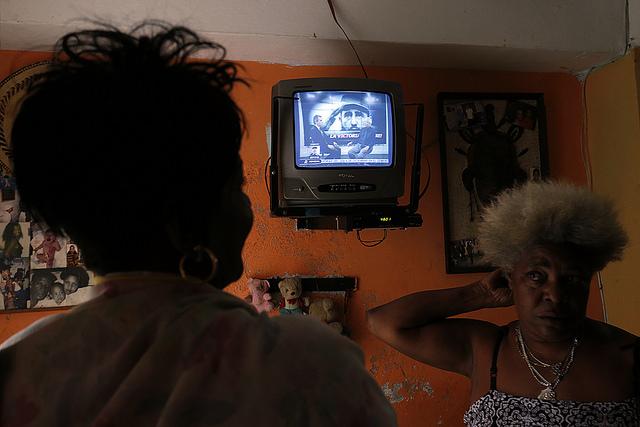Dos mujeres comentan el fallecimiento de Fidel Castro, el sábado 26 de noviembre, en La Habana, mientras siguen por televisión la programación especial sobre la muerte de quien dirigió Cuba entre 1959 y 2006. Crédito: Jorge Luis Baños/IPS