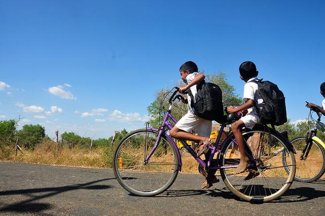 Niños se trasladan en bicicleta desde su casa a la escuela en Welikanda, en Sri Lanka, donde se instalaron muchas personas desde el final de la guerra civil en 2009. Crédito: Amantha Perera/IPS.