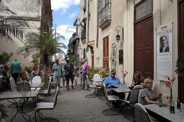 El boom de la llegada de turistas, en especial procedentes de Estados Unidos, como los sentados fuera de los restaurantes en una calle de La Habana, ha sido insuficiente para evitar la caída en la recesión de Cuba durante 2016. Crédito: Jorge Luis Baños/IPS