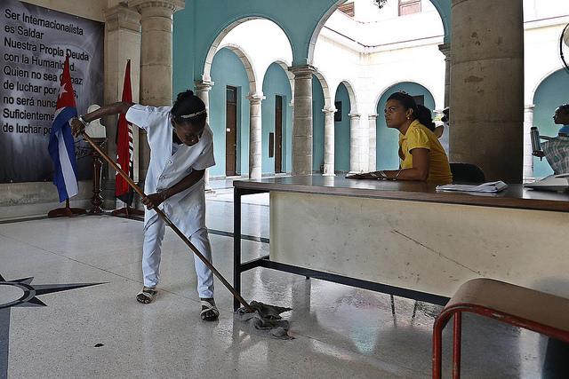 Una empleada de la limpieza y otra de la recepción, mientras desarrollan su labor en un organismo del gobierno en la capital de Cuba. Crédito: Jorge Luis Baños/IPS