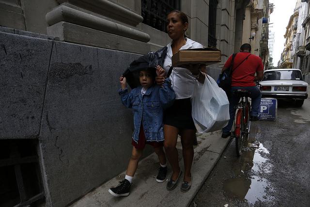 Una madre camina junto a su hija, en la Habana Vieja, en la capital de Cuba,  tras recogerla de la escuela. En este país caribeño, las tareas del cuidado están a cargo casi exclusivo de las mujeres. Crédito: Jorge Luis Baños/IPS