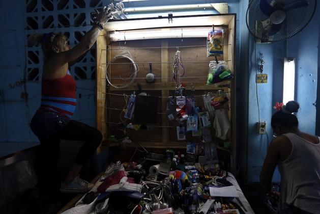 Dos mujeres preparan los productos para la venta en un pequeño puesto dentro de un edificio en La Habana. El envío de dinero o productos por familiares desde el exterior ha hecho prosperar estos negocios privados en Cuba. Crédito: Jorge Luis Baños/IPS