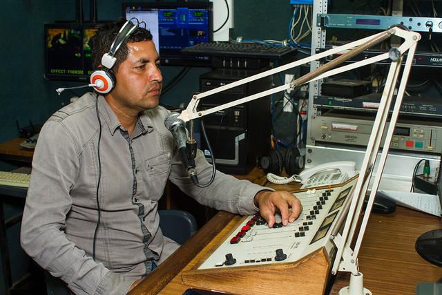 Wilfredo Hernández durante la transmisión de uno de los noticieros radiales de Izcanal Radio Y Televisión, un proyecto surgido en 2003 en Nueva Granada, en el oriente de El Salvador. La emisora comunitaria fue la única que se expandió con un canal de televisión. Crédito: Edgardo Ayala/IPS