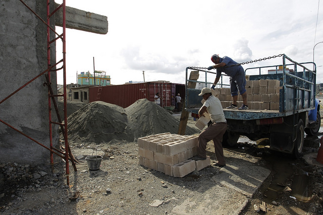 Trabajadores descargan materiales para la reconstrucción de un edificio afectado por el huracán Matthew, en el malecón de la histórica ciudad de Baracoa, en la oriental provincia Guantánamo, en Cuba. Crédito: Jorge Luis Baños/IPS