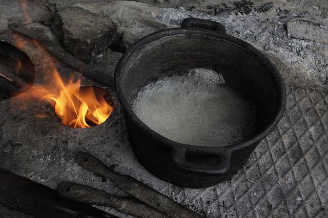 Unas 100.000 familias, mayormente rurales, usan aún leña para cocinar alimentos y otros usos domésticos, en fogones como en este donde hierve agua, en el hogar de Isabel Laurencio y Dagoberto Herrera, en Blanquizal de la Güira, en el oriente de Cuba. Crédito: Jorge Luis Baños/IPS