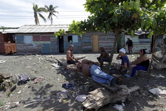 Vecinos de localidad periurbana de La Playa descansan a la sombra de un arbusto, en medio de la contaminada duna formada en la desembocadura del río Macaguaní, llamada localmente tibaracón, próxima a la ciudad de Baracoa, en la costa del oriente de Cuba. Crédito: Jorge Luis Baños/IPS