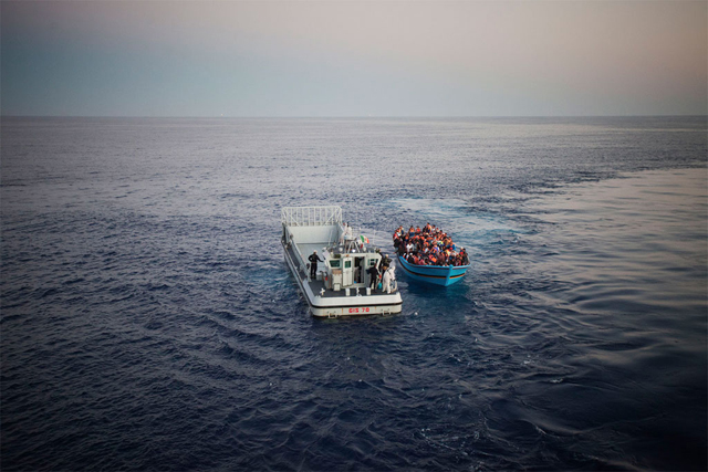 Migrantes zarpan del norte de África y arriesgan su vida para llegar a Europa en embarcaciones repletas. Muchos de ellos necesitan protección internacional. En la fotografía, un barco recibe asistencia de la Marina italiana en el mar Mediterráneo. Crédito: A. D'Amato/UNHCR