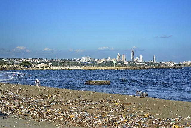 Un hombre busca objetos entre los desechos esparcidos en las contaminadas arenas de la playa El Gringo, en el municipio de Bajos de Haina, el principal centro industrial y portuario de República Dominicana. Crédito: Dionny Matos/IPS