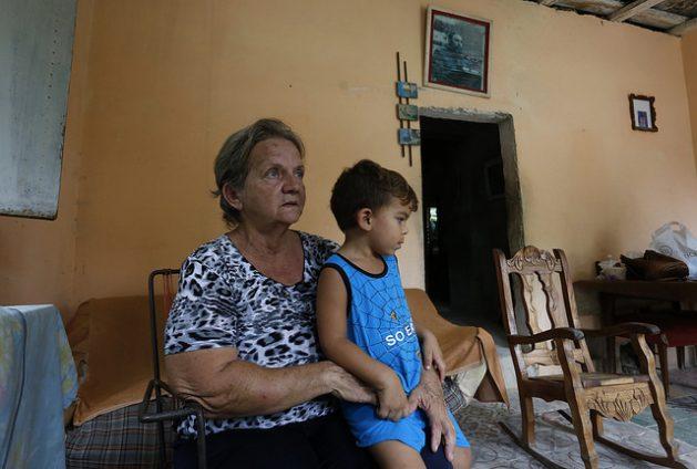 Águeda Celina Vidal, en su vivienda en Guanabacoa, un municipio de la periferia de la capital de Cuba, con el nieto, al que ella y su hijo tienen al cuidado cuatro días a la semana, gracias al dictamen de una jueza de familia. Crédito: Jorge Luis Baños/IPS