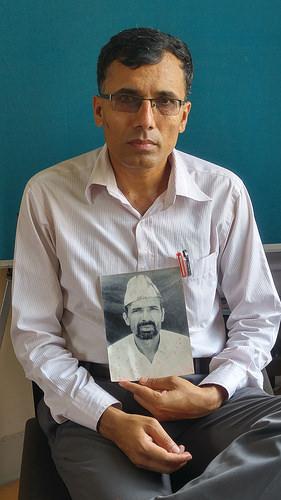 Suman Adhikari, presidente de la Plataforma Común de Víctimas del Conflicto de Nepal, muestra una fotografía de su padre asesinado en 2002. Crédito: Marty Logan/IPS.