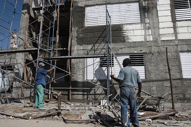 Dos trabajadores laboran en la reconstrucción de un edificio que resultó dañado por el paso del huracán Sandy en 2012 por la ciudad de Santiago de Cuba, en el oriente de la isla caribeña. Crédito: Jorge Luis Baños/IPS