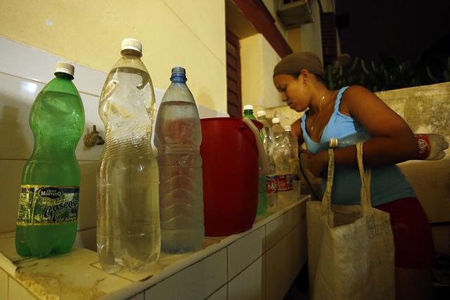 Una residente en uno de los municipios de La Habana organiza en su hogar los envases con agua potable que acaba de acarrear desde la calle, tras días sin suministro del recurso en su vivienda en la capital de Cuba. Crédito: Jorge Luis Baños/IPS