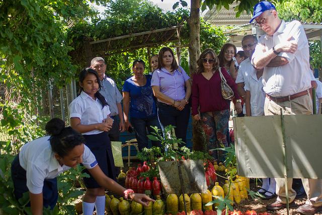 El representante regional para América Latina y el Caribe de la FAO, Julio Berdegué (derecha), y otros visitantes escuchan las explicaciones de dos alumnas de la escuela de Pepenance, una aldea de El Salvador, sobre la producción de vegetales en el huerto del centro. Crédito: Edgardo Ayala/IPS