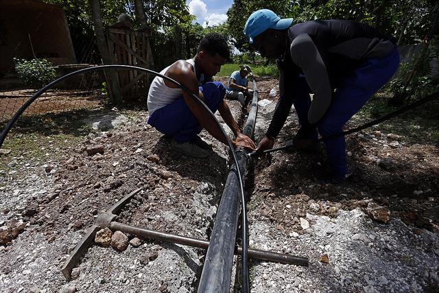Operarios instalan tubos de la red hidráulica de agua potable en un área de viviendas del municipio de La Lisa, uno de los que conforman La Habana, en Cuba. Crédito: Jorge Luis Baños/IPS