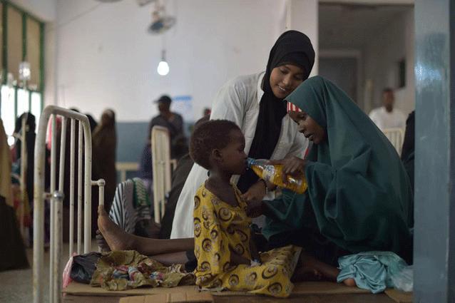 Una mujer le da a su hija una bebida con sales rehidratantes en un hospital en Mogadiscio, Somalia. Ese país sufre una grave sequía y la ONU redobló la respuesta humanitaria para evitar que empeore la situación (marzo de 2017). Crédito: Tobin Jones/UN Photo