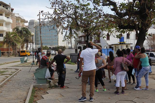 Contrario a lo habitual, unas pocas personas aguardan en una plaza cercana a la sede de la Embajada de Estados Unidos en La Habana, al fondo a la izquierda, para intentar realizar trámites, después que la expedición de visas quedó suspendida el 29 de septiembre. Crédito: Jorge Luis Baños/IPS
