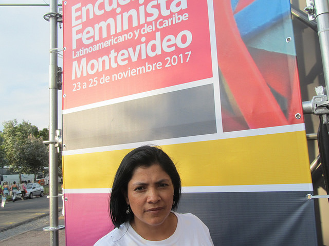 Yanet Caruajulca, activista peruana por el derecho al agua y a un ambiente sano, ante un cartel del 14 Encuentro Feminista Latinoamericano y del Caribe en la capital de Montevideo, donde uno de los ejes fue el análisis de los ataques con sesgo de género de los que son víctimas las defensoras de derechos en la región. Crédito: Mariela Jara/IPS