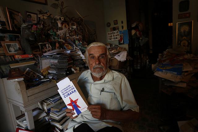 Enrique López Oliva, un periodista jubilado y profesor en activo, muestra la portada de un libro dentro de su estudio en el municipio Playa, uno de los que conforman la capital de Cuba. Crédito: Jorge Luis Baños/IPS