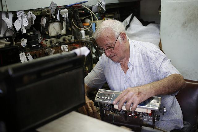 Roberto Sordo, de 84 años y reconvertido en trabajador por cuenta propia tras su jubilación, repara equipos de radio en un local arrendado del municipio Centro Habana, en la capital de Cuba. Crédito: Jorge Luis Baños/IPS