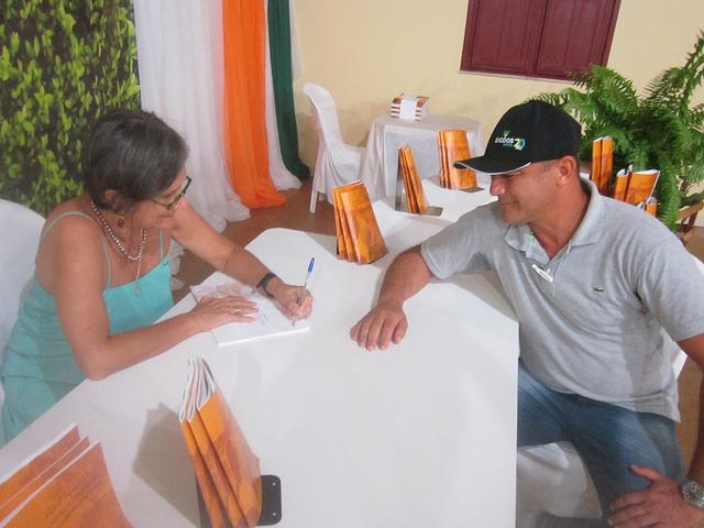 """Thais Corral, cofundadora del proyecto Adapta Sertão, mientras autografía el libro que cuenta la historia de la iniciativa para Josaniel Azevedo, director de la Cooperativa Agroindustrial de Itaberaba. El programa """"amplió nuestros horizontes"""", con la visión de sostenibilidad ambiental, asegura el productor en Pintadas, en el estado brasileño de Bahia, en el nordeste de Brasil. Crédito: Mario Osava/IPS"""