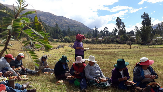 Mujeres y hombres de la comunidad de Paropucjio, en las alturas de los Andes peruanos, en la región de Cusco, comparten el almuerzo preparado tras terminar la faena comunitaria de construir uno de los 80 pequeños invernaderos, en los que un número igual de mujeres podrá cultivar vegetales orgánicos pese a las temperaturas extremas de la zona. Crédito: Mariela Jara/IPS