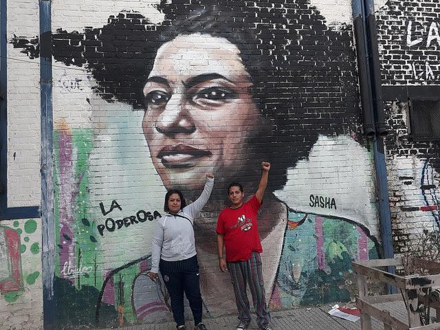 Lucy Mercado y Marcos Basualdo, dos integrantes de la organización social de La Poderosa, posan delante de un mural en la Villa 21, un barrio precario de Buenos Aires, que homenajea a Marielle Franco, la política y activista de derechos humanos brasileña que fue asesinada en marzo en Río de Janeiro. Crédito: Daniel Gutman/IPS