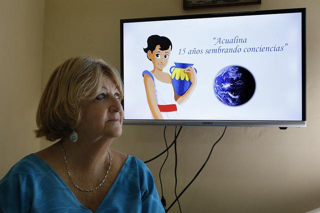 Ángela Corvea ante la imagen de Acualina, el proyecto educativo que creó hace 15 años en Cuba para enseñar a reducir los riesgos ambientales, incluidos los climáticos, en un país insular donde los impactos del incremento de las temperaturas son muy perceptibles. Crédito: Jorge Luis Baños/IPS