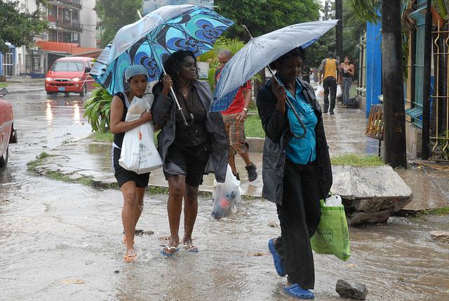 Varias mujeres caminan en medio de la lluvia hacia sus hogares provistas con víveres, como parte de sus previsiones ante la inminente llegada a Cuba del huracán Gustav, en 2008, en un barrio de La Habana. Crédito: Jorge Luis Baños/IPS