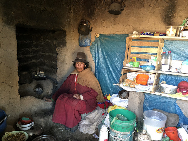 Maruja Anco, de 48 años, dentro de su actual vivienda en la aldea altoandina peruana de Quinsalakaya, donde su cocina carece de ducto para liberar el humo, que al esparcirse por el interior afecta la salud de la familia. Ella integra una de las 30 familias que están por mudarse a una vivienda que la reparará del frío de las heladas y del humo. Crédito: Annie Solís/IPS