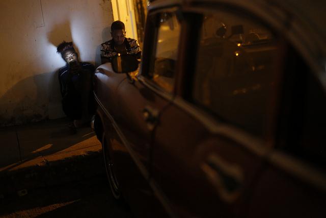 A la luz de las pantallas de sus celulares y los faros de un vehículo, dos jóvenes cubanos acceden a Internet a través de una red inalámbrica en el barrio de La Víbora, en el municipio de Diez de Octubre, en La Habana. Crédito: Jorge Luis Baños/IPS