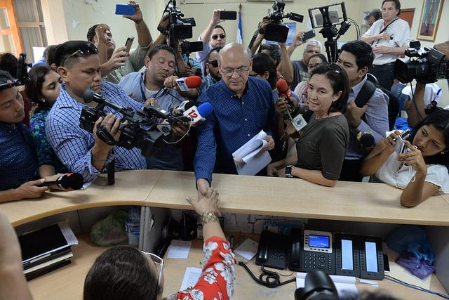 Carlos Fernando Chamorro, entre un enjambre de colegas periodistas, presenta ante la Fiscalía General de la República de Nicaragua, el 19 de diciembre, la denuncia sobre el asalto y confiscación de las instalaciones y equipos del Confidencial y otros medios informativos por efectivos policiales, cinco días antes. Crédito: Jader Flores/IPS