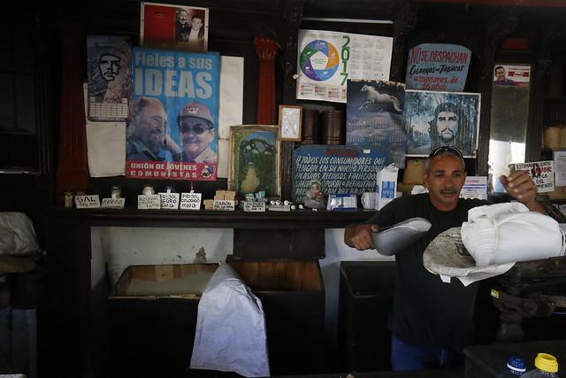 Un empleado expende productos subsidiados en el interior de un establecimiento estatal, decorado con imágenes alegóricas a la revolución cubana, en el barrio del Vedado, en La Habana. La escasez de alimentos preocupa a la población cubana, ante el empeoramiento de la crisis económica. Crédito: Jorge Luis Baños/IPS